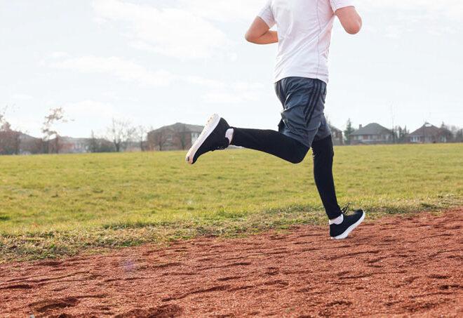 グラウンドを走る男性の後ろ姿
