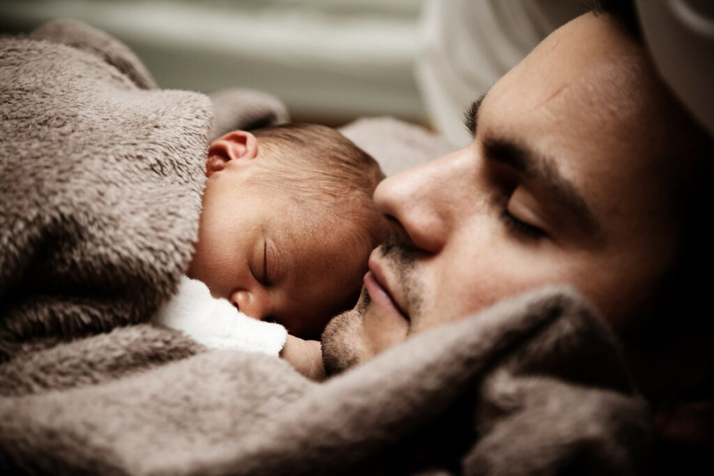 子供と添い寝して疲労回復してる男性