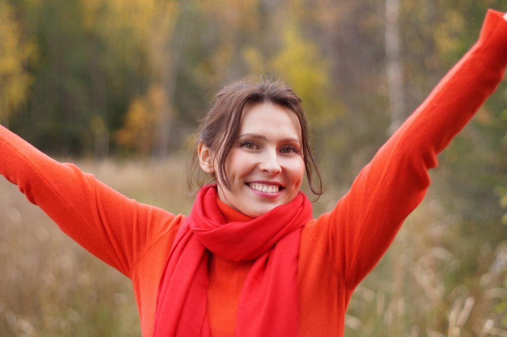 両手をあげた赤い服着た女性が笑顔