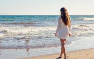 綺麗な女性が海沿いを歩いている