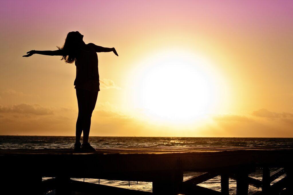 夕日に照らされる綺麗な女性が立っている